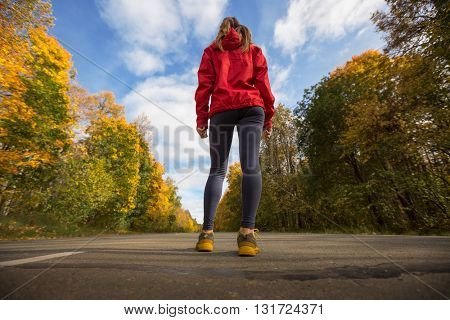 Woman athlete stands on an asphalt road in an autumn forest