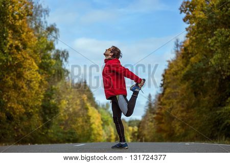 Man warms up and stretches on an asphalt road in an autumn forest