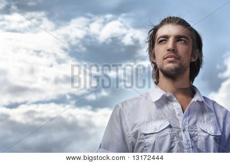 Handsome young man posing over blue sky.