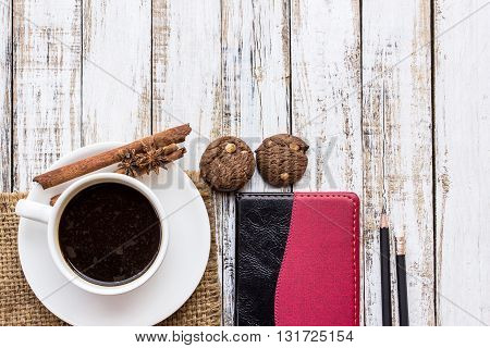 Coffee and coffee cupcookiespices and notebook on white wooden table background. top view. Coffee in the morning