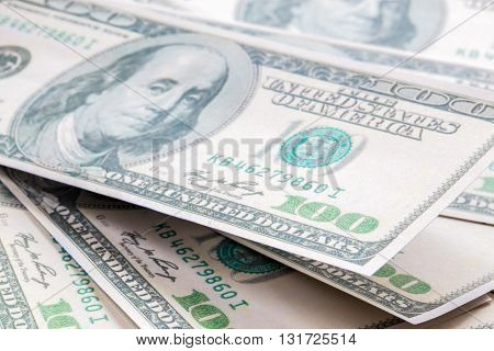 Closeup of a pile of one hundred dollar banknotes in daylight