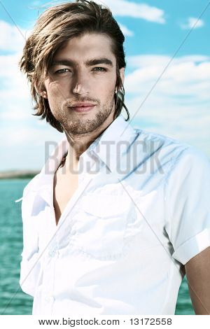 Handsome young man posing over sea and blue sky.