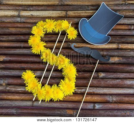 Sign of dollar currency symbol made of fresh summer yellow flowers.