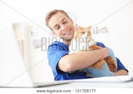 Cheerful young veterinarian is holding a cat and smiling. He is sitting at desk and stroking animal with joy
