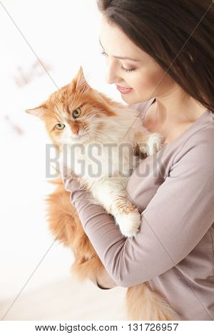 Attractive young woman is holding a cat. She is standing and smiling. The girl is looking at her animal with love