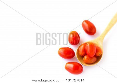 Red tometos in wooden spoon on a white background
