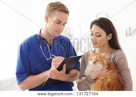 Skillful young veterinarian is writing prescription for ill animal. He is standing and carrying folder. Woman is holding a cat and smiling