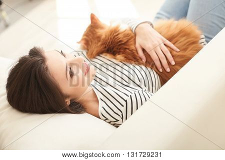 Attractive young woman is lying on couch and relaxing. She is holding her cat and stroking it with love. The lady is dreaming and smiling at home