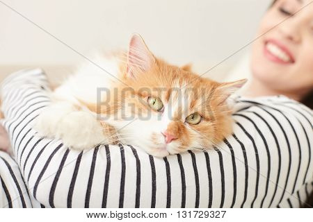 Beautiful girl is having rest with a cat at home. She is holding it and smiling. Focus on animal lying with relaxation