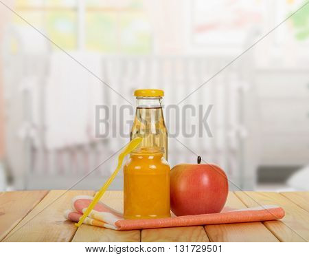 Jar of baby puree, juice bottle, apple and spoon on a background of the kitchen.