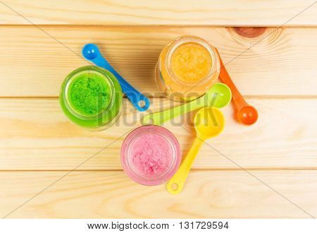 Three jars of different baby puree and spoon on a background of light wood.