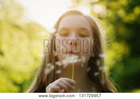 teen girl blowing dandelion to the camera, focus on girl