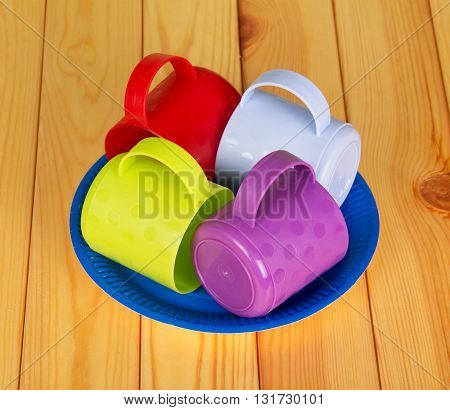 Colored plastic mugs and disposable plates on light wood background.