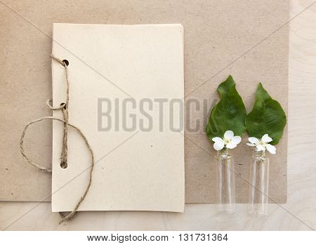 Open vintage handmade sketchbook with white bird-cherry flowers over wooden table background. Mock up retro style. Old paper notepad. White flowers in small flacons. Vintage retro mockup.