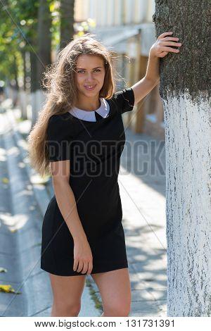 Full length portrait of glamorous girl in black dress standing near tree