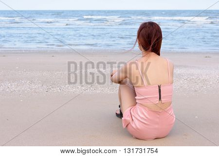 Asian woman sitting on the beach looking at the sea and sky