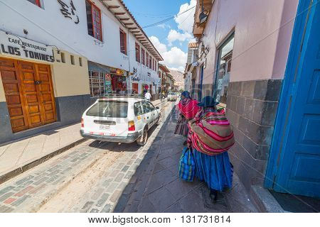 Cusco Peru - September 3 2015: Two traditionally dressed women carrying bundle in a street of Cusco town Peru. Rear view.