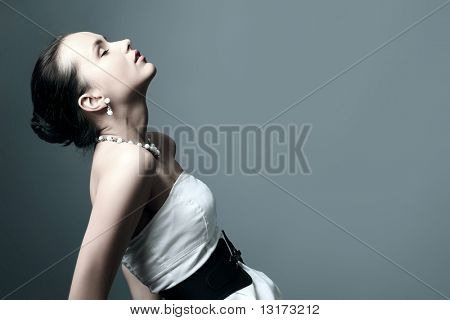 Fashion photo, a model is  posing over grey background