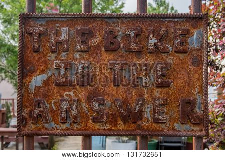 The Bike is the Answer Rusted Sign on rusted fence