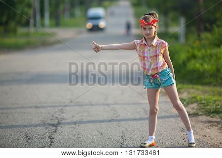 Little girl hitchhiking along a road.