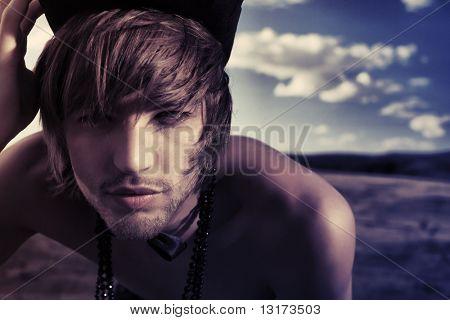 Toma de moda de un atractivo joven posando topless en sombrero de copa y pajarita sobre paisaje.