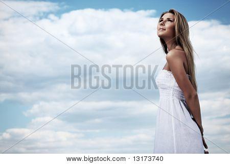 Beautiful young woman posing over summer sky.