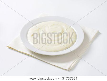 plate of semolina pudding on white napkin