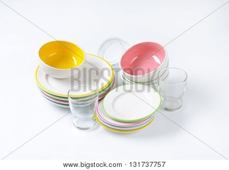 set of rimmed plates, bowls and glasses on white background