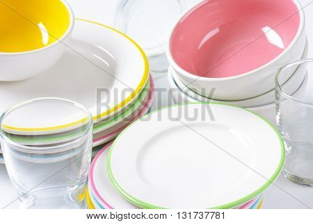 set of rimmed plates, bowls and glasses - close up