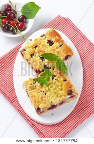 two slices of cherry crumb cake on white cutting board