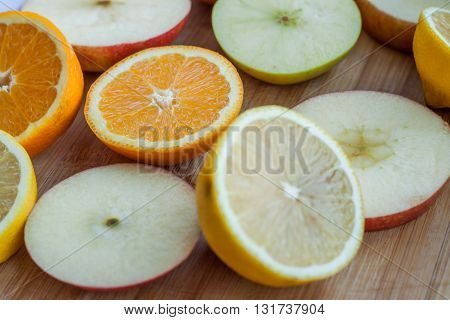 sliced juicy fruits on a wooden board. sliced orange. sliced apple. sliced lemon