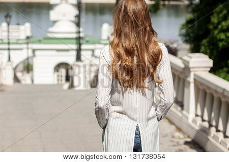 Beautiful Girl Standing With Her Back On The Stairs In The Park And Looking At River