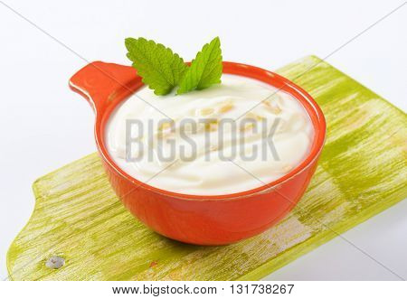 bowl of fresh yogurt with fruit on wooden cutting board - close up