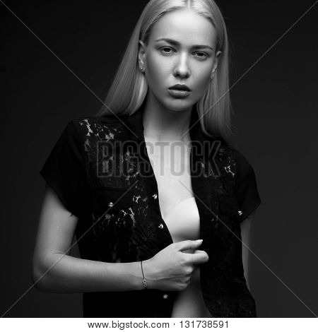 sexy fashion model with long hair, young European attractive, beautiful eyes, full lips, perfect skin is posing in studio for glamour vogue test photo shoot showing different poses. Picture taken in the studio on a gray background. Black and white photo