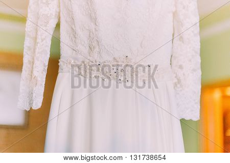 Close up of the hanging in hotel room wedding dress detail.