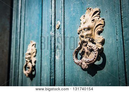 Antique door knockers of an old door.