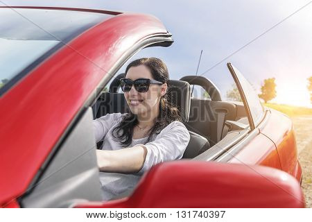 Happy woman driving a car on a country road at sunset.