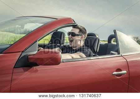 Angry man driving a car. Toned image.