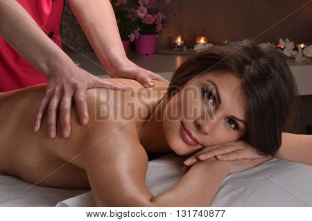 Beautiful latin woman getting massage at beauty center spa. Looking at camera.