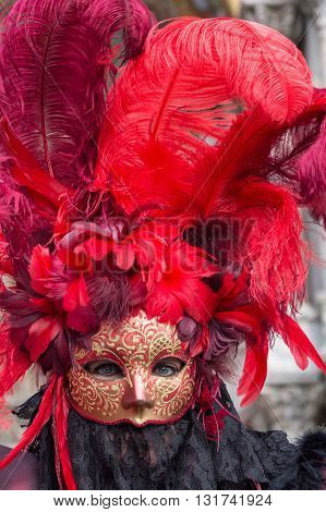 Venice, Italy - February 15, 2015: Portrait of an unidentified woman wearing a magnificent red costume at the Carnival of Venice, in Italy.