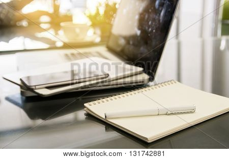 White pen on notepad with blurred laptop and smartphone background