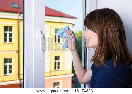 Young Woman Cleaning Window With Rag At Home