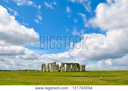 Stonehenge site during a sunny day with clouds in the background
