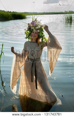Attractive Sad Woman with Wreath of Flowers walking in water of lake. Russian traditional holiday celebration