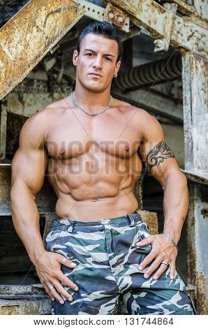Handsome young muscle man shirtless leaning on metal structure, looking at camera