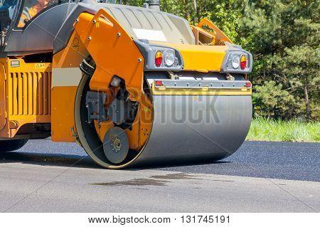 Road orange  roller flattening new asphalt, close-up
