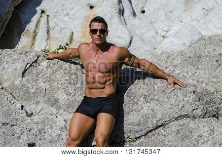 Attractive young muscle man shirtless against white rocks, looking to a side.