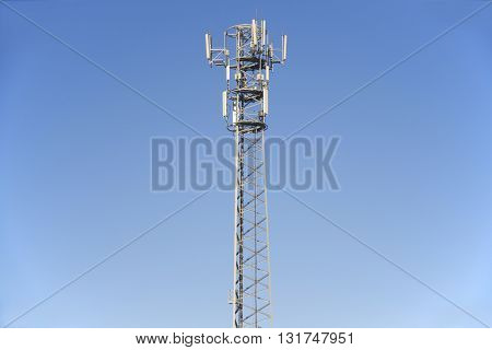 Phone transmitter tower on background blue sky