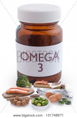 Omega 3 rich foods next to a pill jar over a white background