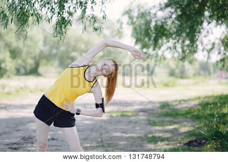 Young fitness woman runner stretching body before run. Sportsman standing under tree.